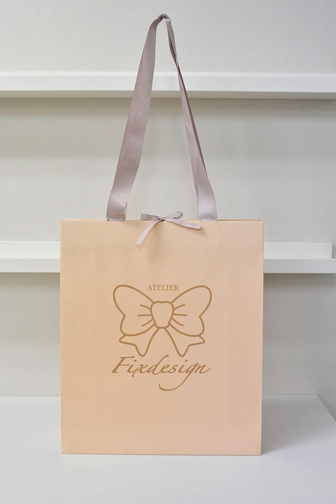 ヌーディーな色と大きなリボンがかわいい紙袋