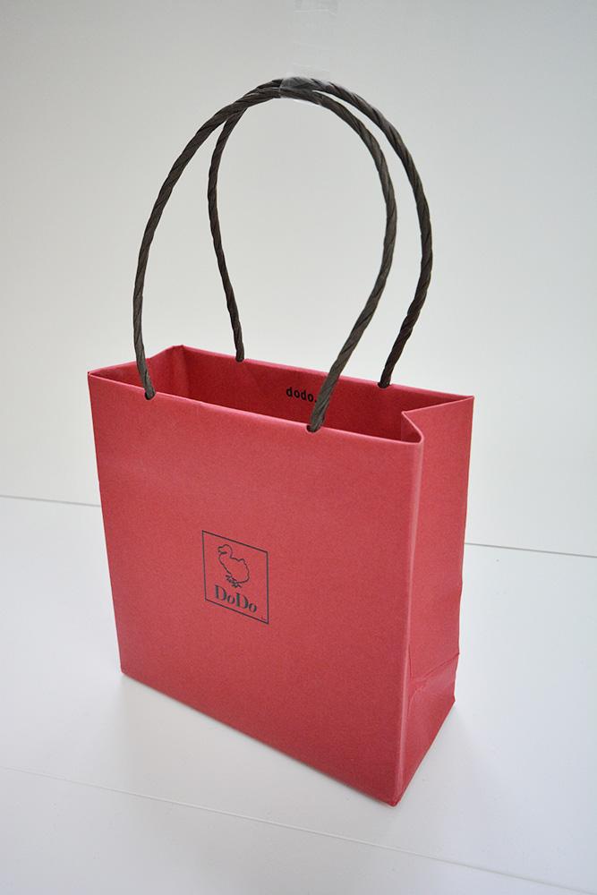 落ちついたシックな赤色にかわいいロゴがはいったお洒落な紙袋