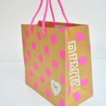 蛍光ピンクのドットと犬がかわいい海外ブランドの紙袋を読む