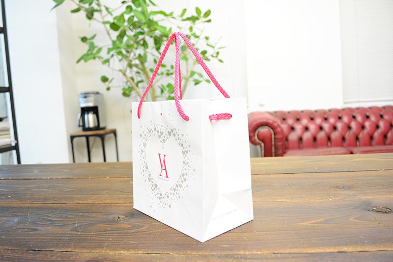 ロゴの周りのキラキラなラメ加工がかわいい紙袋