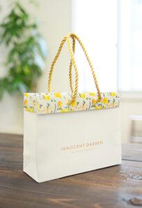 裏面を折り返して花柄を見せる紙袋