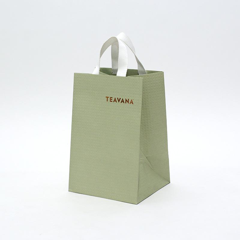 コンパクトなハンドルの柔らかグリーンな紙袋を読む