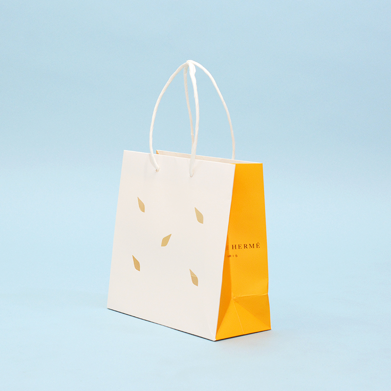 印象的な切り抜きデザインのマチオレンジ紙袋を読む