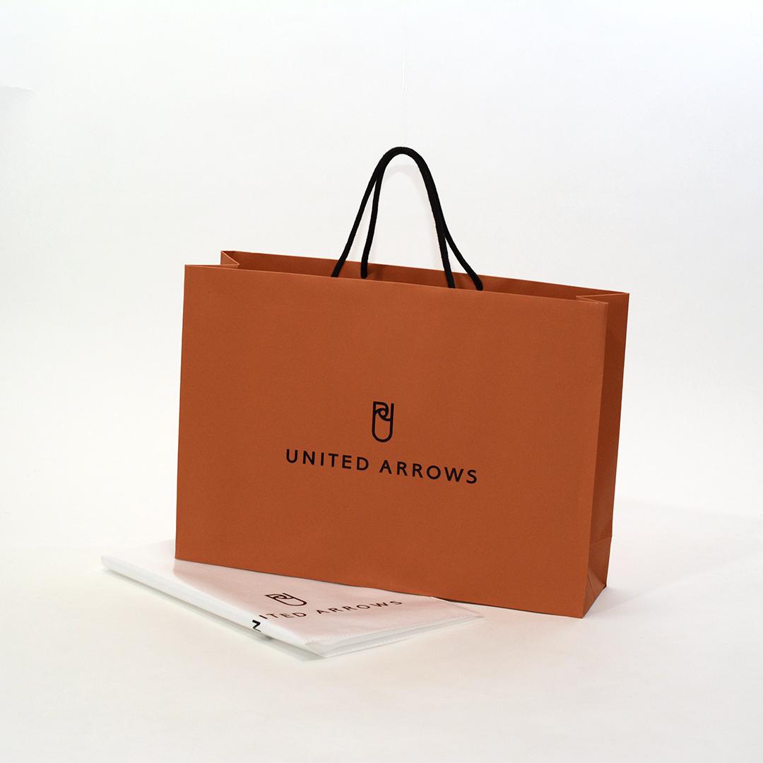絶妙なオレンジが目を引く、シンプルで高級感がある紙袋