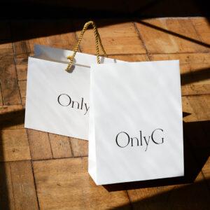 ゴージャスなゴールドの持ち手とシンプルな黒ロゴの紙袋と宅配袋