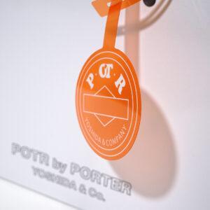 オレンジのチャームとポリ袋がユニークなパッケージ