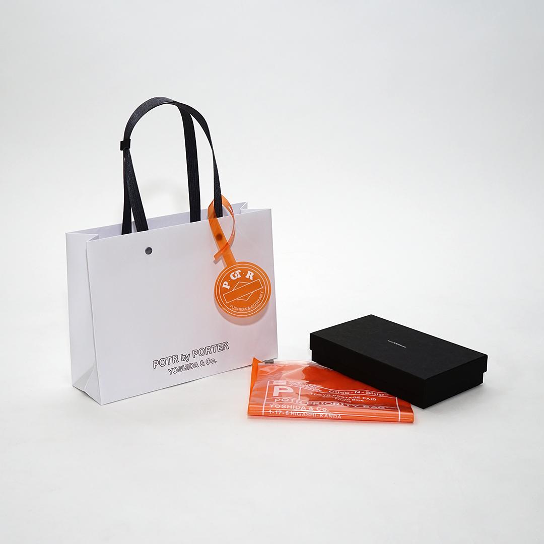 オレンジのチャームとポリ袋がユニークな老舗ブランドの紙袋を読む